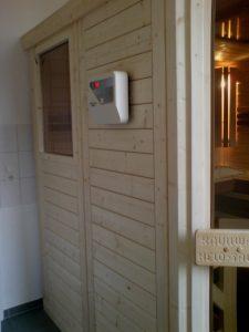 Sauna mit Eckeinstieg und seitlichem Fensterelement und externer Steuerung.